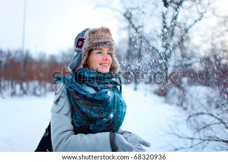Portrait of beautiful young girl throwing snow in the air - stock photo