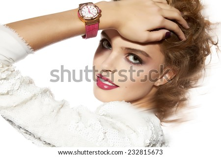 Portrait of beautiful young girl with a bright evening make-up perfect skin and blue eyes, red lips, nice smile blonde curly hair dressed in a white jacket with sequins with  hand watch - stock photo