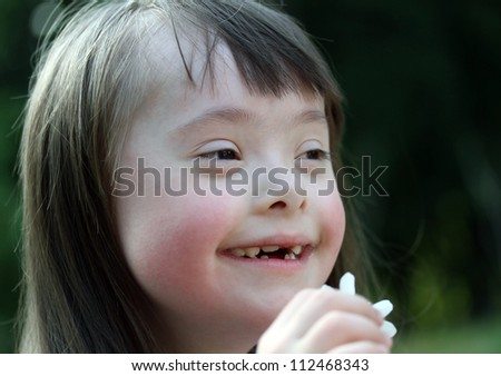 Portrait of beautiful young girl with flowers in the park - stock photo