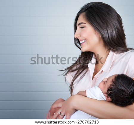 Portrait of beautiful young happy mother having fun with her little newborn baby at home, enjoying first day of motherhood, love and happiness concept - stock photo