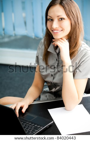 Portrait of beautiful young happy smiling business woman at office - stock photo