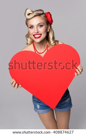 Portrait of beautiful young happy smiling woman holding heart symbol, dressed in pin-up style. Caucasian blond model posing in retro fashion and vintage concept studio shoot, on grey background. - stock photo
