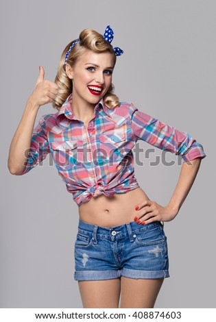 Portrait of beautiful young happy smiling woman, showing thumb up gesture, dressed in pin-up style. Caucasian blond model posing in retro fashion and vintage concept studio shoot, on grey background. - stock photo