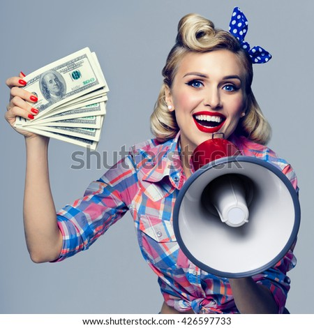 Portrait of beautiful young happy smiling woman with money and megaphone, dressed in pin-up style. Caucasian blond model posing in retro fashion and vintage concept studio shoot. - stock photo