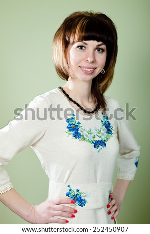 Portrait of beautiful young lady in artistic exclusive embroidered dress - stock photo