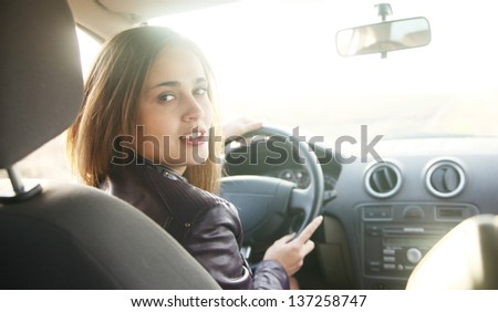 Portrait of beautiful young latin hispanic woman in the new car - indoor - stock photo