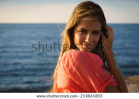 Portrait of beautiful young latina woman on holidays, sitting near sea and smiling at camera - stock photo