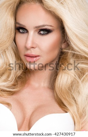 Portrait of beautiful young long-haired blonde with green eyes,, amazing sensory mouth and face, sensual looks at the camera, she is sexy and feminine - stock photo