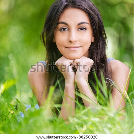 portrait of beautiful young long-haired woman lying on grass in park and propping up her face with hands - stock photo