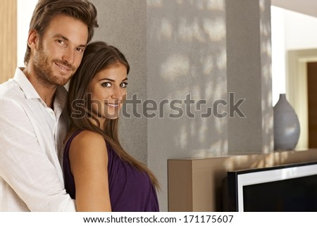 Portrait of beautiful young loving couple embracing at home in living room. - stock photo