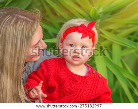 Portrait of beautiful young mother having fun in the park with her cute stylish little daughter, happy family enjoying spring time - stock photo