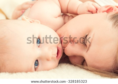Portrait of beautiful young mother with a baby. Mother kisses the child. - stock photo