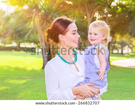Portrait of beautiful young mother with cute little daughter on hands spending summer day in fresh green park, having fun outdoors, love and happiness concept - stock photo