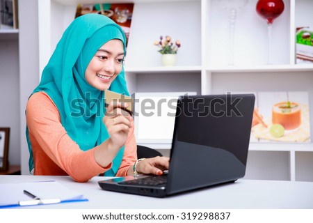 portrait of beautiful young muslim woman browsing internet on laptop while holding a credit card at living room - stock photo
