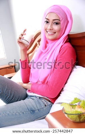 portrait of beautiful young muslim woman holding a glass of milk for breakfast on bed - stock photo