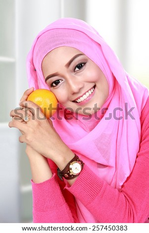 portrait of beautiful young muslim woman holding an orange - stock photo