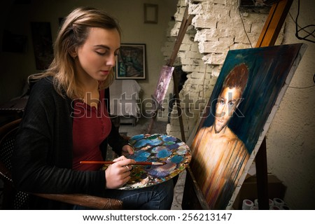 Portrait of beautiful young painter holding paintbrush and color palette while working on oil painting in art studio. - stock photo