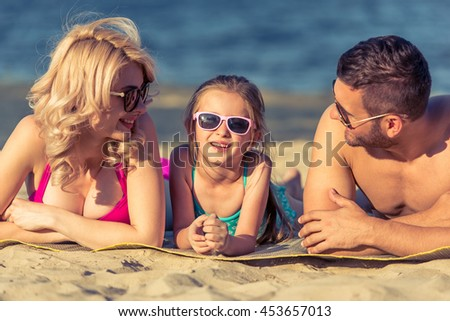 Portrait of beautiful young parents and cute little girl in swimsuits and sun glasses smiling, lying on the sunny beach. Parents are looking at their daughter - stock photo