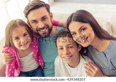 Portrait of beautiful young parents, their cute little daughter and son looking at camera and smiling, sitting on sofa at home - stock photo