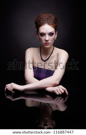 portrait of beautiful young redhead woman at dark reflecting surface - stock photo