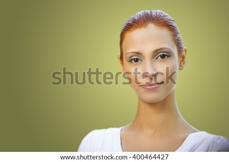 Portrait of beautiful young redhead woman wearing white blouse on green background - stock photo