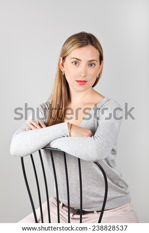 Portrait of beautiful young Russian girl sitting in a chair - stock photo