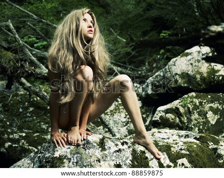 Portrait of beautiful young savage in the jungle - stock photo