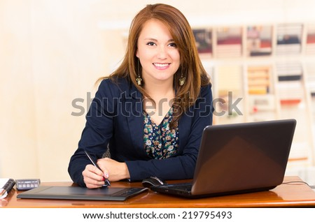 portrait of beautiful young secretary working from desk using tablet and laptop - stock photo