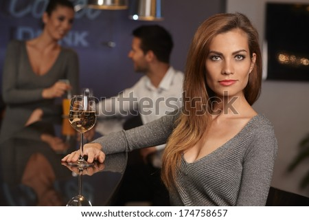 Portrait of beautiful young sexy woman sitting in bar, drinking wine. - stock photo