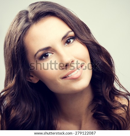 Portrait of beautiful young smiling brunette woman - stock photo