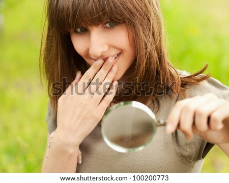 Portrait of beautiful young smiling teenager girl with magnifier at summer green park - stock photo