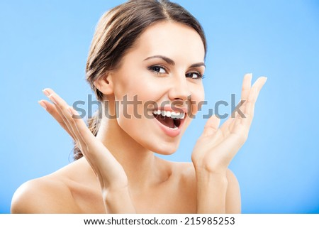 Portrait of beautiful young smiling woman, over blue  - stock photo