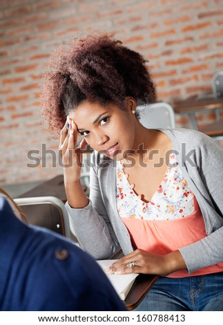 Portrait of beautiful young student thinking while giving test in classroom - stock photo