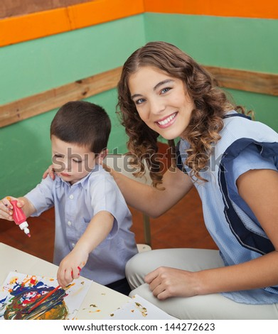 Portrait of beautiful young teacher with student painting in classroom - stock photo