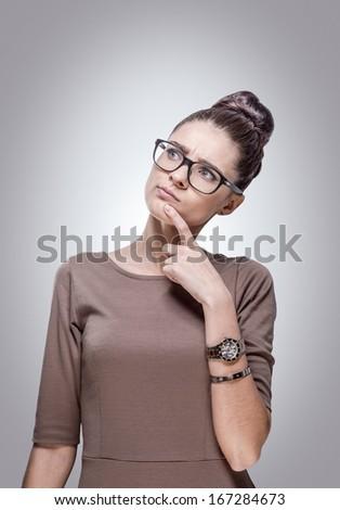 Portrait of beautiful young thinking woman. - stock photo