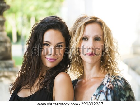 Portrait of Beautiful Young Woman and beautiful Middle Aged Woman  In The Park, that are mother and daughter - stock photo