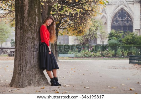 portrait of beautiful young woman, blond model with long hair posing in red blouse and black skirt, photoshoot in Paris - stock photo