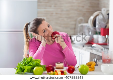 Portrait of beautiful young woman bored with her diet eating an apple while cake is standing in front of her on the table - stock photo