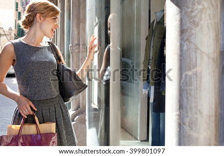 Portrait of beautiful young woman carrying shopping bags in city fashion stores, joyfully smiling and looking at shop windows, sunny outdoors. Consumer girl, exclusive expensive lifestyle exterior. - stock photo
