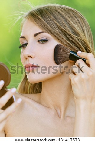 Portrait of beautiful young woman causes powder to face, against green of summer park. - stock photo