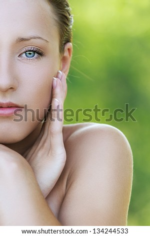 Portrait of beautiful young woman close up with bared shoulders, against background of summer green park. - stock photo