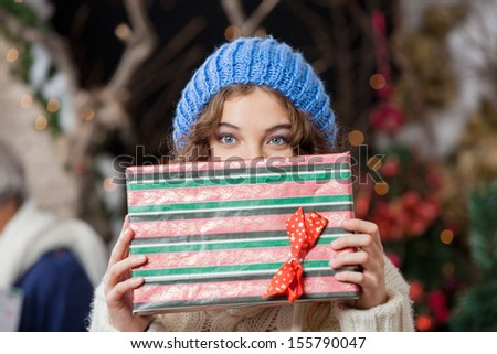 Portrait of beautiful young woman covering face with Christmas present at store - stock photo