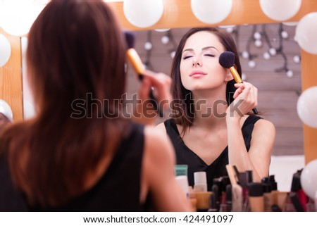 portrait of beautiful young woman doing makeup - stock photo