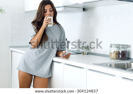 Portrait of beautiful young woman drinking coffee and using her mobile phone at home. - stock photo