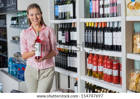 Portrait of beautiful young woman holding bottle of alcohol at supermarket - stock photo
