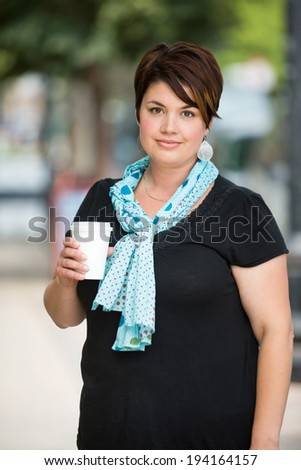 Portrait of beautiful young woman holding disposable coffee cup outdoors - stock photo
