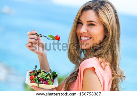 Portrait of beautiful young woman holding green salad outdoors at seaside. - stock photo