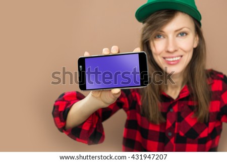 Portrait of beautiful young woman holding smartphone, focus on phone - stock photo