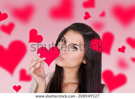 Portrait of beautiful young woman holding while kissing heart shape paper - stock photo