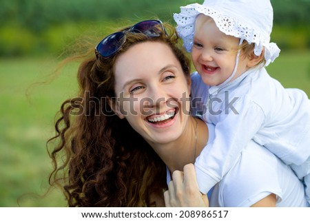 Portrait of  beautiful young woman hugging her little baby - stock photo
